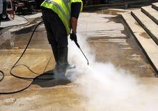 Nettoyage du trottoir de la rue avec à eau sous pression photographie stock libre de droits