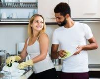 Nettoyage interracial de couples dans la cuisine Image stock