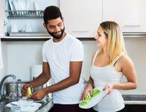 Nettoyage interracial de couples dans la cuisine Photos libres de droits
