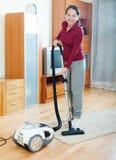 Nettoyage mûr heureux de femme avec l'aspirateur Images stock