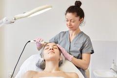 Nettoyage ultrasonique de visage La jeune fille a l'épluchage d'ultrason Le Cosmetologist fait la procédure pour le rajeunissemen photos stock