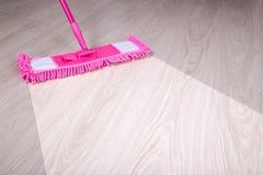 Nettoyant, avant et après le concept - plancher en bois avec le balai rose Photos stock