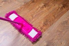 Nettoyant le plancher de parquet avec le balai rose - avant ensuite images libres de droits