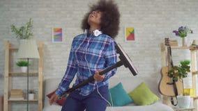 Nettoyer à l'aspirateur positif expressif de femme au foyer de jeune femme d'Afro-américain chante la danse d'amusement et jouer  clips vidéos