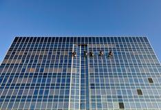Nettoyeurs d'hublot sur le gratte-ciel images stock