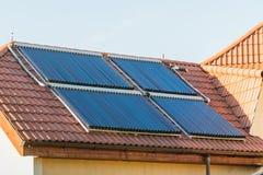 Nettoyez à l'aspirateur le système de chauffage solaire de l'eau de collecteurs sur le toit rouge de la maison photo libre de droits