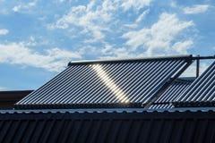Nettoyez à l'aspirateur le système de chauffage solaire de l'eau sur le toit de maison images libres de droits