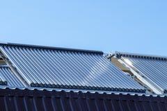 Nettoyez à l'aspirateur le système de chauffage solaire de l'eau sur le toit de maison image libre de droits