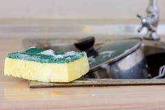 Nettoyez l'éponge dans l'évier image libre de droits