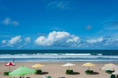 Nettoyez la plage tropicale vide avec des lits pliants sous le parapluie et une belle vue de l'océan calme sous le ciel bleu Photo libre de droits