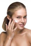 Nettoyez la verticale de beauté d'un blond en appliquant une crème Photographie stock