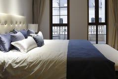 Nettoyez le lit dans une chambre à coucher de deux fenêtres images stock