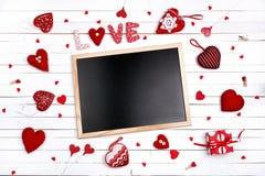 Nettoyez le tableau noir avec des coeurs sur le fond en bois blanc L'espace f Photographie stock