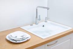 Nettoyez les plats près de l'évier photographie stock libre de droits