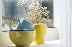 Nettoyez les tasses et les tasses colorées près de la fenêtre blanche Photographie stock libre de droits
