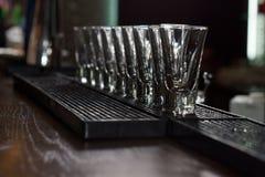 Nettoyez les verres à liqueur vides alignés sur la barre image stock
