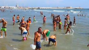 Nettuno, Italy People having fun playing on the beach at summer footage. Nettuno, Italy - Aug 2015: People having fun playing on the beach at summer footage stock footage