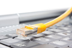 Network cable and laptop keyboard Royalty Free Stock Image