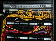 Network Cables. Plugged into patch panels and an ethernet switch in a rack stock image
