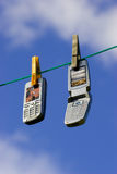 Network of cell phones. Two Cell Phones Drying on Clothesline / Network of wireless devices. Clipping path for displays included Royalty Free Stock Image