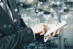 Network and communication concept. Side view of young businessman using smartphone with social media icons on blurry office interior background. Network and stock image