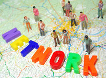 Network concept. Social network represented by different miniature people and colorful network message on map Royalty Free Stock Photo