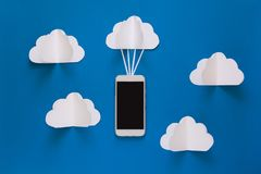 Data communications and cloud computing network concept. Smart phone flying on paper cloud. Network connection and cloud storage technology concept. Data Royalty Free Stock Images