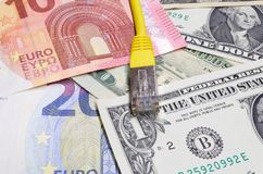 Network connection plug and mixed currencies - euro and american dollars. Close up photo of network connection plug and mixed currencies - euro and american stock image