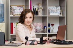 Network distributor of cosmetics works on a laptop. Young woman sitting at office table, laid out on the table cosmetics Royalty Free Stock Photography