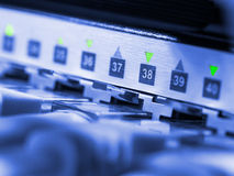 Network equipment. Closeup view of blue toned network hub and cables Royalty Free Stock Photography