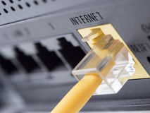 Network equipment. Network yellow cable connected to a router or modem Royalty Free Stock Image