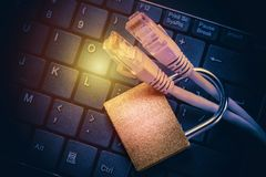 Network ethernet cables in padlock on black computer keyboard. Internet data privacy information security concept. Toned image Stock Image