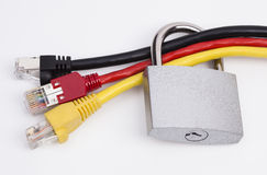 Network security. Image shows network cables in black, red and yellow with a lock royalty free stock photography