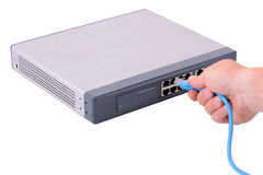 Network switch. Hand plugging an rj45 connector in to a network hub Royalty Free Stock Images