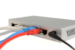 A network switch is connected colored cables. On white Royalty Free Stock Images