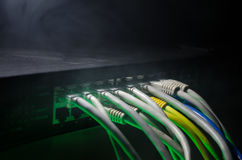Network switch and ethernet cables, symbol of global communications. Colored network cables on dark background with lights and smo. Ke. Selective focus. Network Stock Image