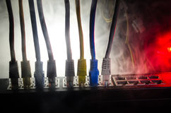 Network switch and ethernet cables, symbol of global communications. Colored network cables on dark background with lights and smo. Ke. Selective focus. Network Stock Images