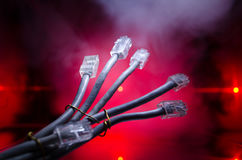 Network switch and ethernet cables, symbol of global communications. Colored network cables on dark background with lights and smo. Ke. Selective focus. Network Royalty Free Stock Images