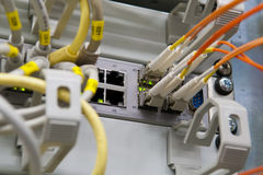 Network switch with fiber glass support. Ethernet switch with labeled cables and optical fiber channel plugs Royalty Free Stock Images