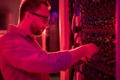 Network technician fixing supercomputer. Serious concentrated bearded network technician in glasses standing at cabinet of mainframe and fixing supercomputer stock image