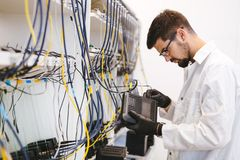 Network technician testing modems. In factory stock photo