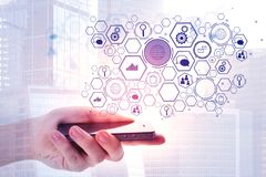 Network and technology concept. Close up of hand holding smartphone with abstract business screen on white city background. Network and technology concept Stock Photos