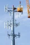 Network Upgrade. Cell phone company upgrading a communications tower Royalty Free Stock Image