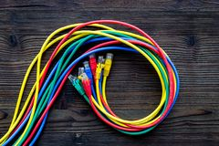 Network wires assorted colors with tips on dark wooden background top view Royalty Free Stock Images