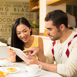 Networking at a cafe. Image of a young couple networking with the digital tablet at a cafeteria Royalty Free Stock Photo