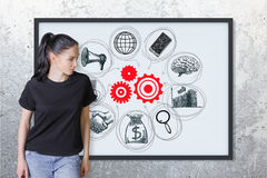 Networking concept. Pensive young european woman looking at picture frame with business sketch. Concrete wall background. Networking concept Royalty Free Stock Image