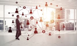 Networking and social communication concept as effective point f. Elegant businessman in 3D office interior and social connection concept. Mixed media Royalty Free Stock Photography