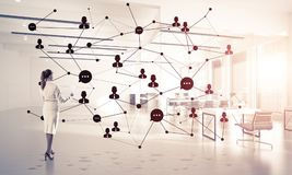 Networking and social communication concept as effective point f. Elegant businesswoman in 3D office interior and social connection concept. Mixed media Royalty Free Stock Photo