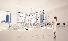 Networking and social communication concept as effective point f. Elegant businesswoman in modern office interior and social connection concept. Mixed media Royalty Free Stock Image