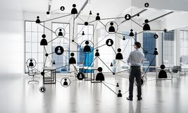Networking and social communication concept as effective point for modern business. Elegant businessman in 3D office interior and social connection concept Royalty Free Stock Photography
